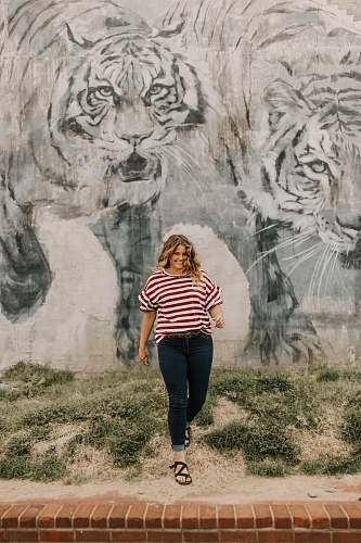 people woman in standing beside tiger-printed wall person