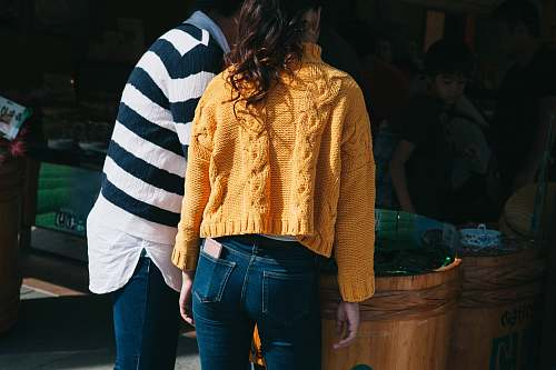 people woman in yellow knit sweater and blue denim jeans stands beside man person