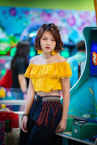 person woman in yellow off-shoulder crop top sitting on green and blue arcade machine people