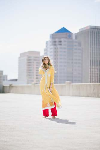 people woman in yellow shalwar kameez standing on concrete floor holding her hair during daytime person