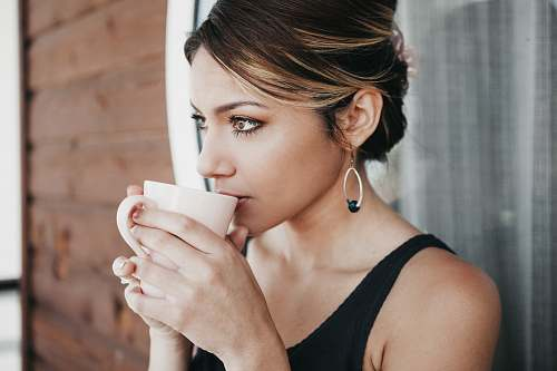 people woman leaning on wall drinking coffee person