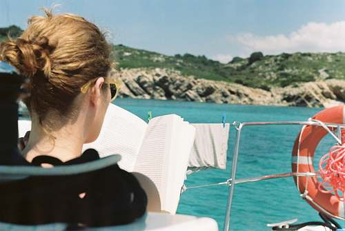 person woman reading book on boat people