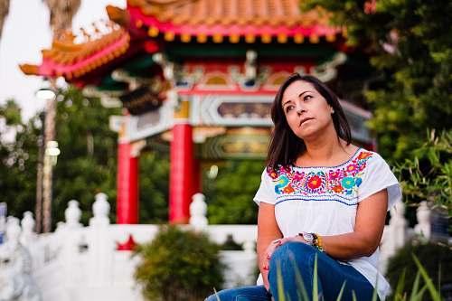 people woman sitting near gazebo and green plants person