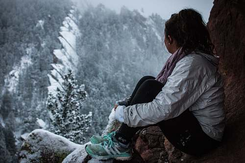 person woman sitting on rock formation under snow people