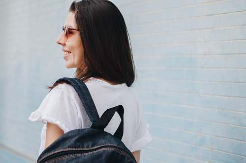 person woman smiling while carrying blue denim backpack people