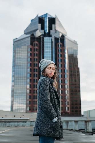 people woman standing behind high rise building during daytime person