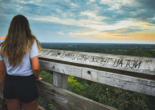 person woman standing in front of wooden fence people