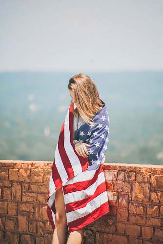 people woman standing leaning on brick wall wrapping body with U.S. flag near body of water person