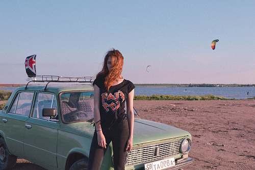 people woman standing near blue car on seashore car