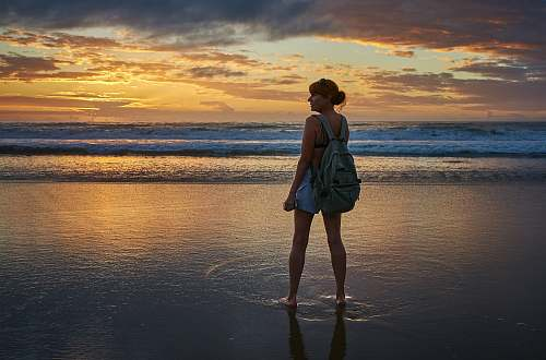 people woman standing near the seashore during golden hour person