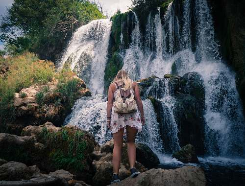 person woman standing near waterfalls people