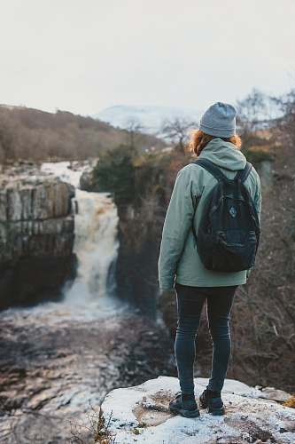 people woman standing on cliff facing waterfall person