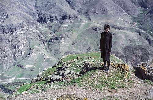 people woman standing on cliff wearing black suit person