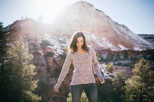 people woman standing on front of mountain sweater