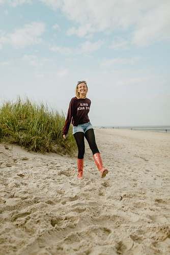 people woman standing on gray sand during daytime person