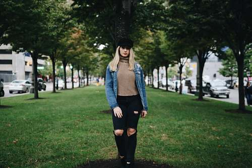 people woman standing on green grass in between of green leafed trees person