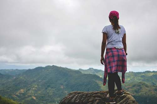 people woman standing on mountain peak facing green mountains at daytime person