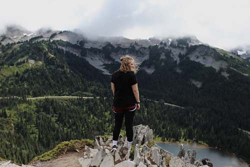 mountain woman standing on rock cliff overlooking trees and body of water with mountains at distance during daytime outdoors