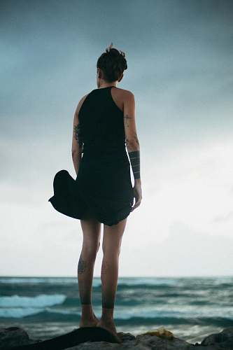 people woman standing on rock looking at the sea during daytime person