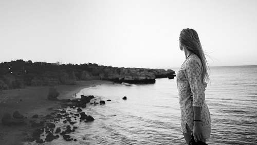 people woman standing on seashore grayscale photography black-and-white