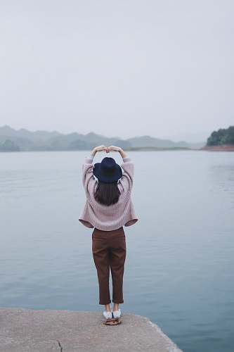 person woman taking a heart pose beside body of water people