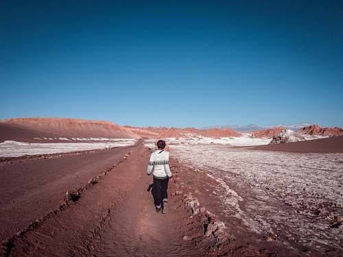 people woman walking along dessert under blue sky during daytime person