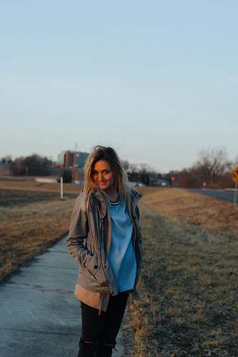 person woman walking on sidewalk near grass field during daytime people