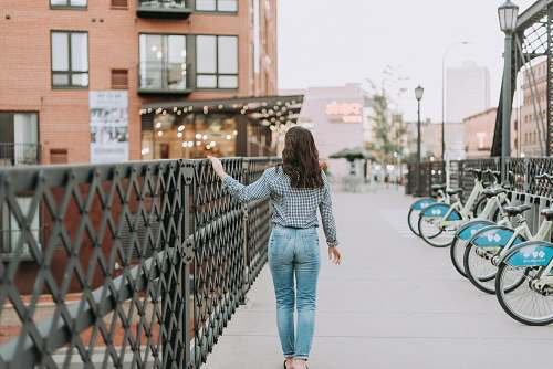 people woman walking outdoors while holding on to black metal railings during day person