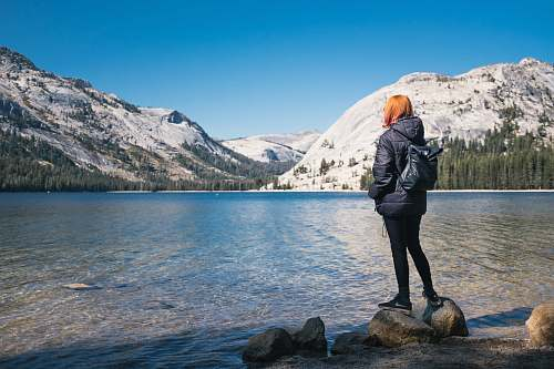people woman wearing black bubble jacket beside lake near hills covered with snow during daytime person