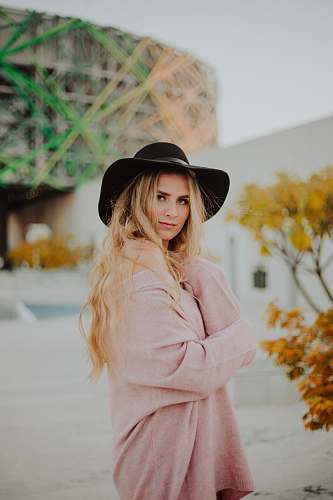 people woman wearing black hat and pink dress person