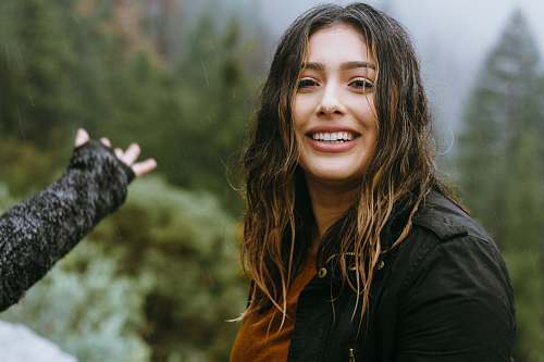 people woman wearing black jacket smiling with forest background person