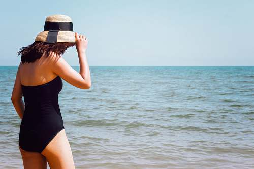 people woman wearing black onepiece swimsuit standing beside seashore at daytime person