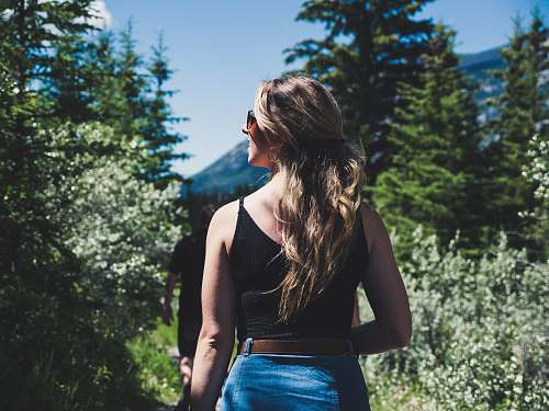people woman wearing black spaghetti strap crop top standing in front of trees while looking left side during daytime person