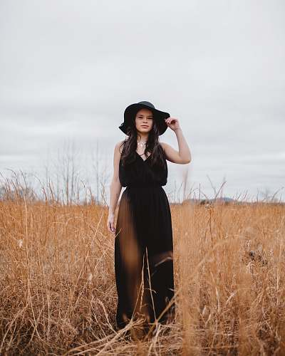 people woman wearing black V-neck spaghetti-strap jumpsuit and black hat standing on brown grass field person