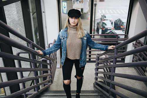 people woman wearing blue denim jacket, brown sweater, black jeans, and hat standing in stair person