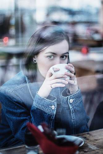 people woman wearing blue denim jacket holding white ceramic teacup person