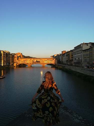 people woman wearing brown and black floral 3/4-sleeved dress standing beside river person