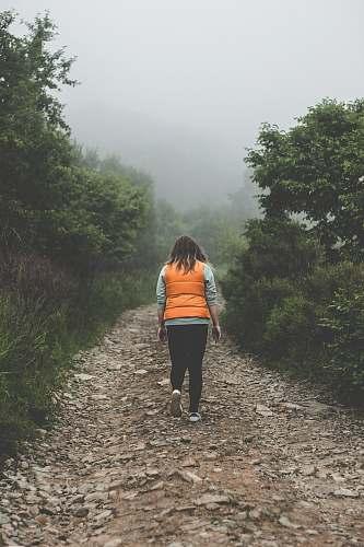 people woman wearing orange life vest walking on pathway during daytime person