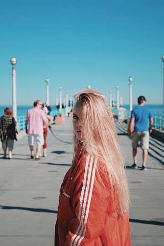 people woman wearing pink windbreaker while walking on dock person