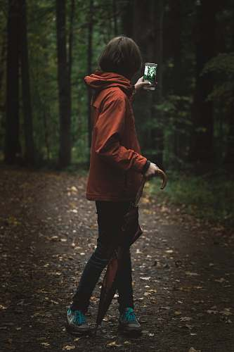 person woman wearing red hoodie holding smartphone near green leafed tree people