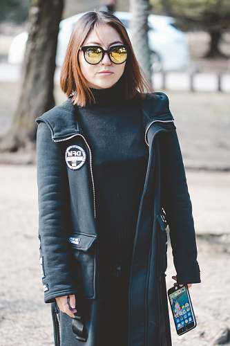 people woman wearing sunglasses holding black Android smartphone person