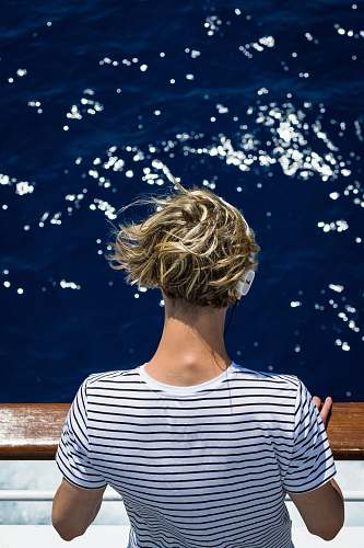 person woman wearing white and black striped shirt looking at water people
