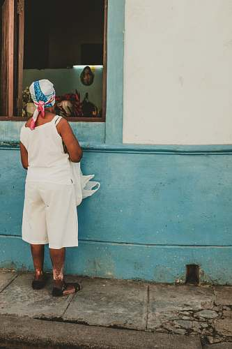 person woman wearing white camisole watching inside the window people