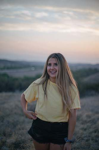 person woman wearing yellow shirt and black shorts at the field people