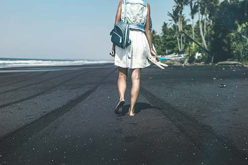 people woman with backpack walking in the beach during daytime person