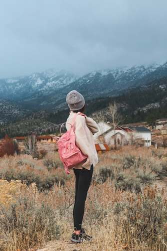 people woman with pink backpack standing near grass overlooking mountains person