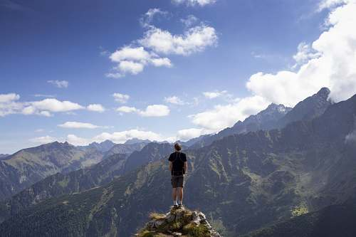 mountain man wearing black shirt and gray shorts on mountain hill beside mountains under white and blue cloudy skies mountain range