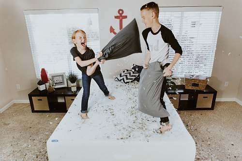 human boy and girl having pillow fight person