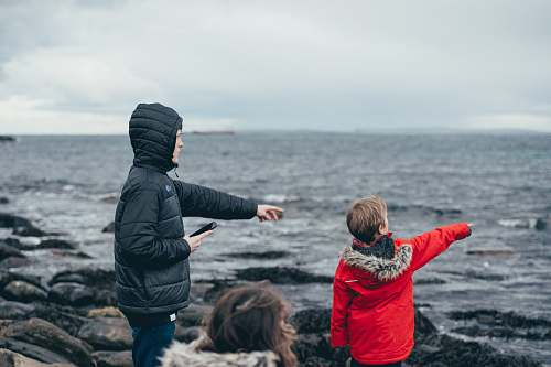 person boy and man pointing on sea taken under white clouds during daytime human