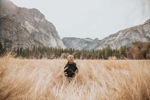 grass boy in black jacket stand on brown grass near mountain human